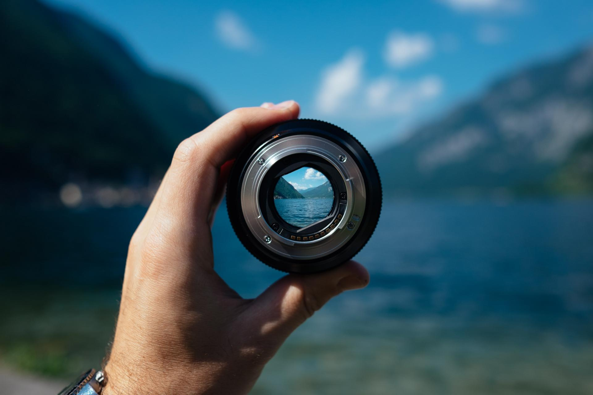 Hand holding lens on the backdrop of a lake - everything is blurred except what is focused by the lens, which is clear